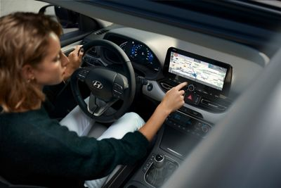 A woman behind the wheel of her Hyundai i30, using the touchscreen.