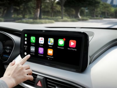 A Hyundai touchscreen display with the Apple Car Play icons displayed on the screen.