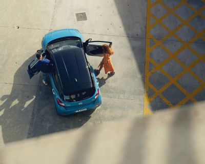View from above, a couple is getting into their blue Hyundai i10.