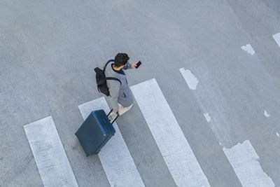 A man in a crosswalk pulling a suitcase and looking at his phone.